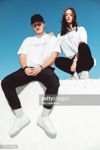 jovem casal elegante sentado na parede de concreto modern fashion portrait - coleção de moda - fotografias e filmes do acervo