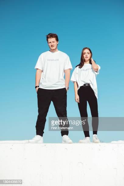 jovem casal da moda em pé em concrete wall modern fashion portrait - coleção de moda - fotografias e filmes do acervo