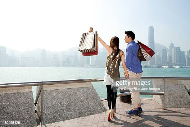 Fashionable young couple with shopping bags enjoying the Victoria Harbor, Hong Kong