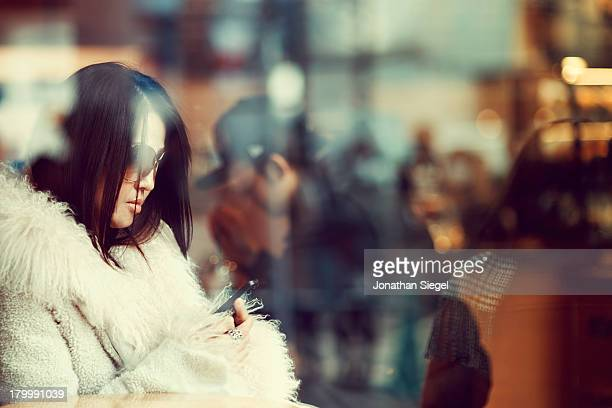 Fashionable young Japanese woman in sunglasses using her mobile phone while waiting inside a cafe in Shibuya, Tokyo.