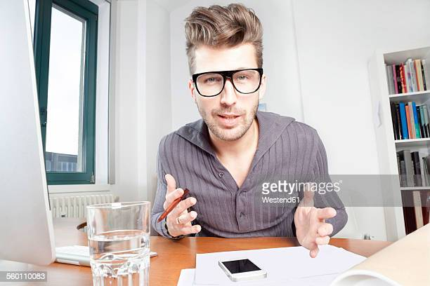 Fashionable young man at his desk in an office