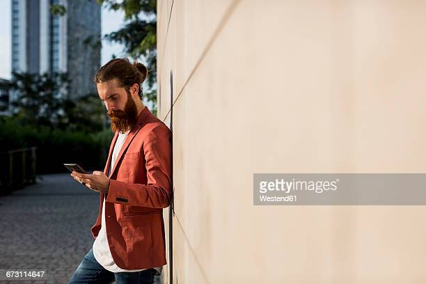 Fashionable young man leaning against wall looking at smartphone