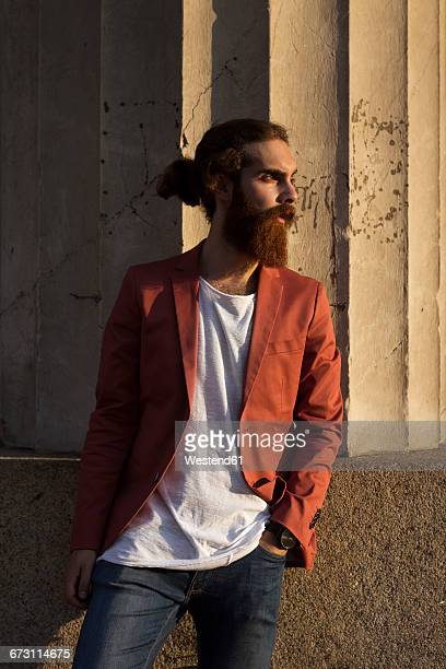 Fashionable young man waiting in front of column