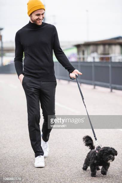 fashionable young man walking with dog on a bridge - yellow hat stock pictures, royalty-free photos & images