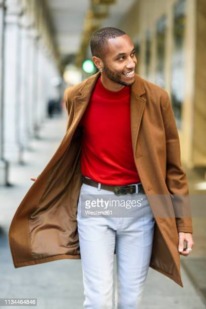 fashionable young man wearing red pullover and brown coat walking along arcade - black coat stock pictures, royalty-free photos & images