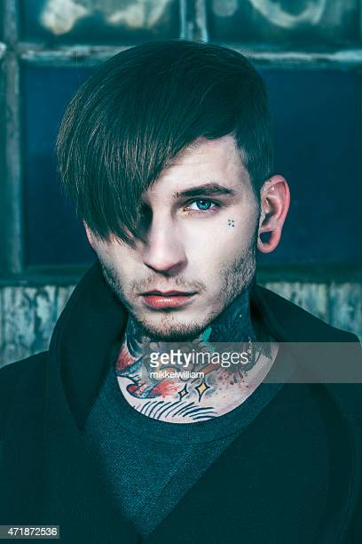 Fashionable young man with funky hair and tattoos on neck