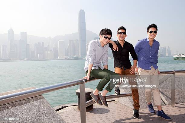 Fashionable young men enjoying the beautiful moment in Victoria Harbor, Hong Kong