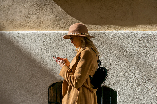 Fashionable young woman at a building using cell phone - gettyimageskorea