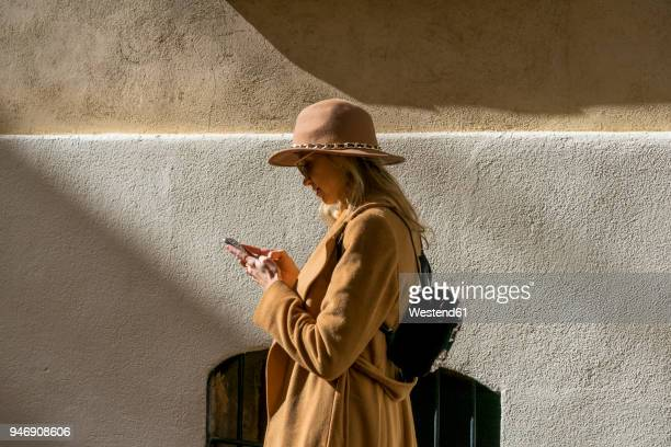 fashionable young woman at a building using cell phone - moda imagens e fotografias de stock