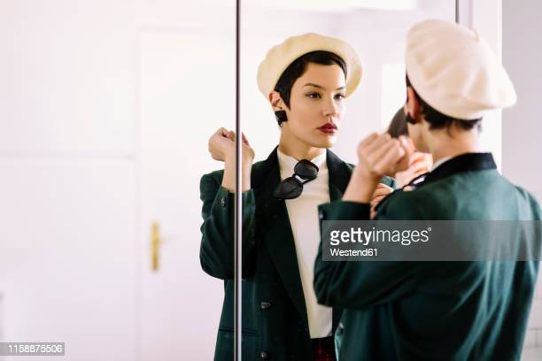 fashionable young woman checking her look in the mirror - ベレー帽 ストックフォトと画像