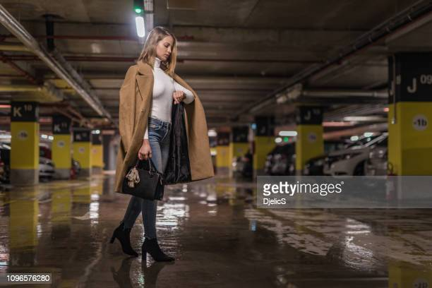 fashionable young woman checking time in a public car garage. - cool cars stock pictures, royalty-free photos & images