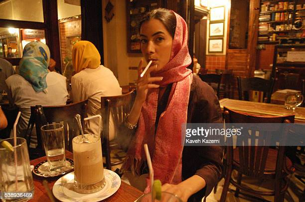 A fashionable young woman enjoying a cigarette and a cafe latte at a coffeeshop in north Tehran Iran 13th June 2003