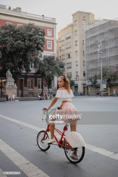 fashionable young woman exploring barcelona with a bicycle - mulher saia curta imagens e fotografias de stock