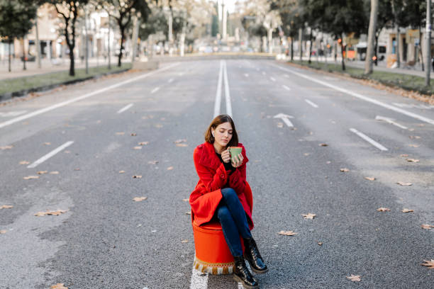 Fashionable young woman holding coffee cup while listening music with eyes closed on street