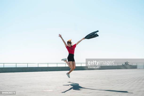 fashionable young woman jumping on waterfront promenade - minirock stock-fotos und bilder