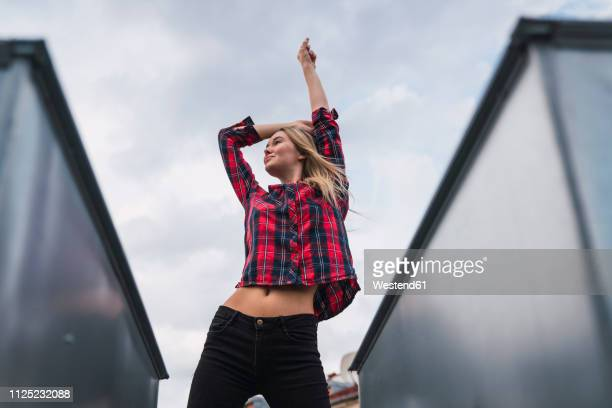 fashionable young woman on rooftop - schottenkaro stock-fotos und bilder