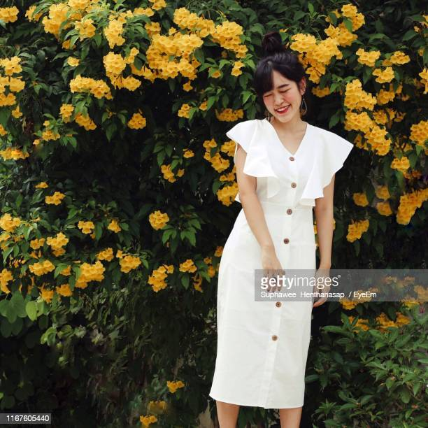 fashionable young woman standing against yellow flowering plants - yellow dress stock pictures, royalty-free photos & images
