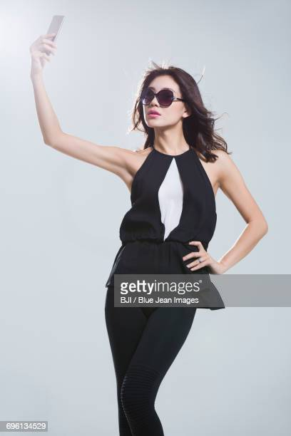 Fashionable young woman taking self portrait with smart phone