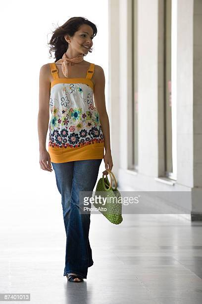 Fashionable young woman walking, full length