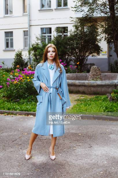 fashionable young woman wearing blue overcoat at public park - overcoat stock pictures, royalty-free photos & images