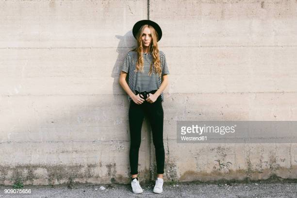 fashionable young woman wearing hat leaning against concrete wall - ボーダーシャツ ストックフォトと画像