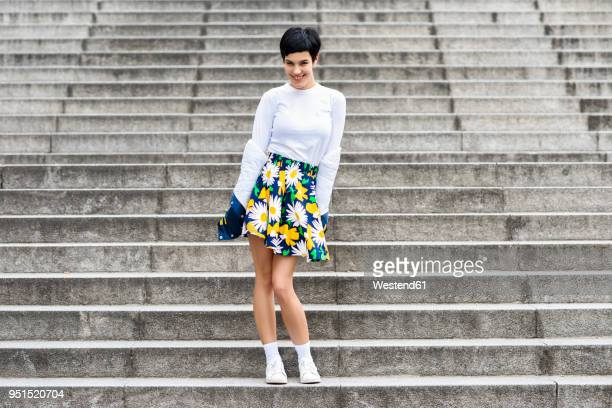 fashionable young woman wearing skirt with floral design standing on stairs - up skirts stock pictures, royalty-free photos & images