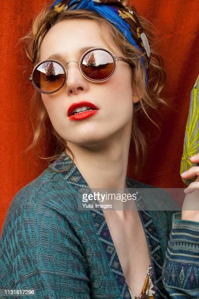 fashionable young woman wearing sunglasses against red fabric - pañuelo de cabeza fotografías e imágenes de stock
