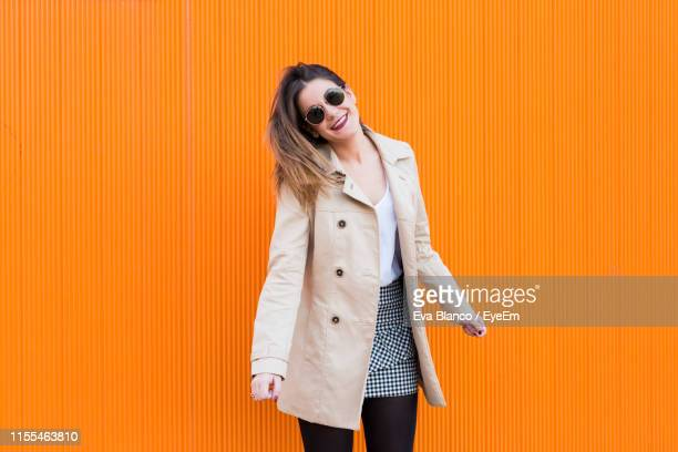 fashionable young woman wearing sunglasses and overcoat while standing against orange wall - hoofd schuin stockfoto's en -beelden