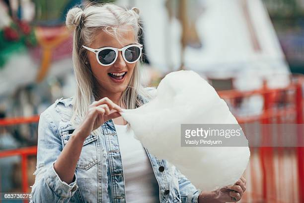 Fashionable young woman wearing sunglasses while eating cotton candy outdoors