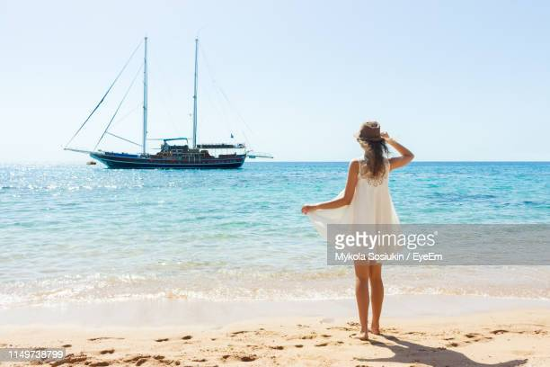 fashionable young woman wearing white dress on shore at beach during summer - 白のドレス ストックフォトと画像