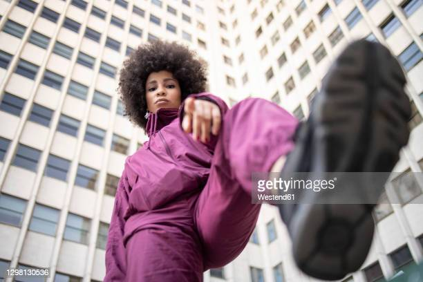 fashionable young woman with cool attitude gesturing against building exterior - black shoe stock pictures, royalty-free photos & images