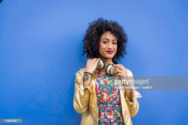 fashionable young woman with curly hair against blue background - sfondo a colori foto e immagini stock
