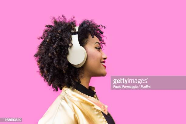 fashionable young woman with curly hair against pink background - luisteren stockfoto's en -beelden