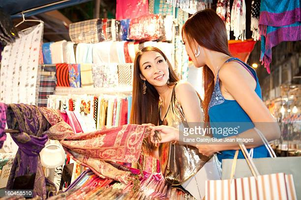Fashionable young women shopping on Temple Street of Hong Kong, night view