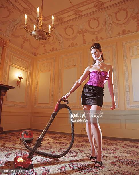 Fashionably dressed woman vacuuming