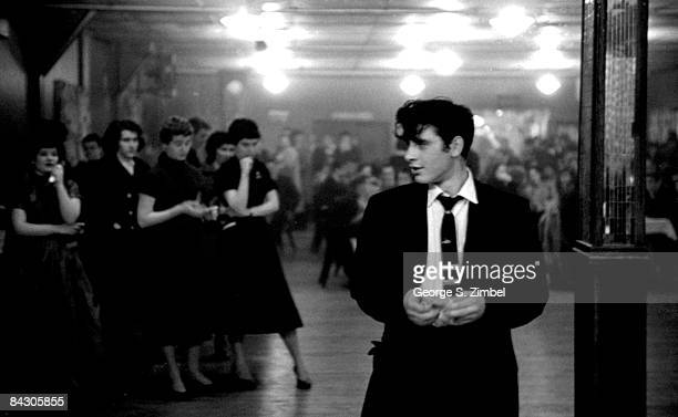A fashionably dressed young man with toussled dark hair stands confidently on the dancefloor while a group of young women wait to be asked for a...