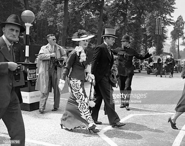 Fashions at the Royal Ascot Races 15 June 1937 Couple crossing the road surrounded by photographers She is wearing a dark full length dress and...