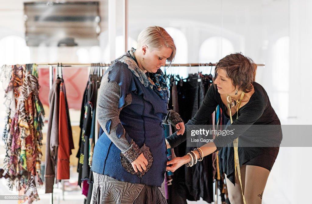 Fasion designer  taking customer measurement in clothing boutique : Foto de stock