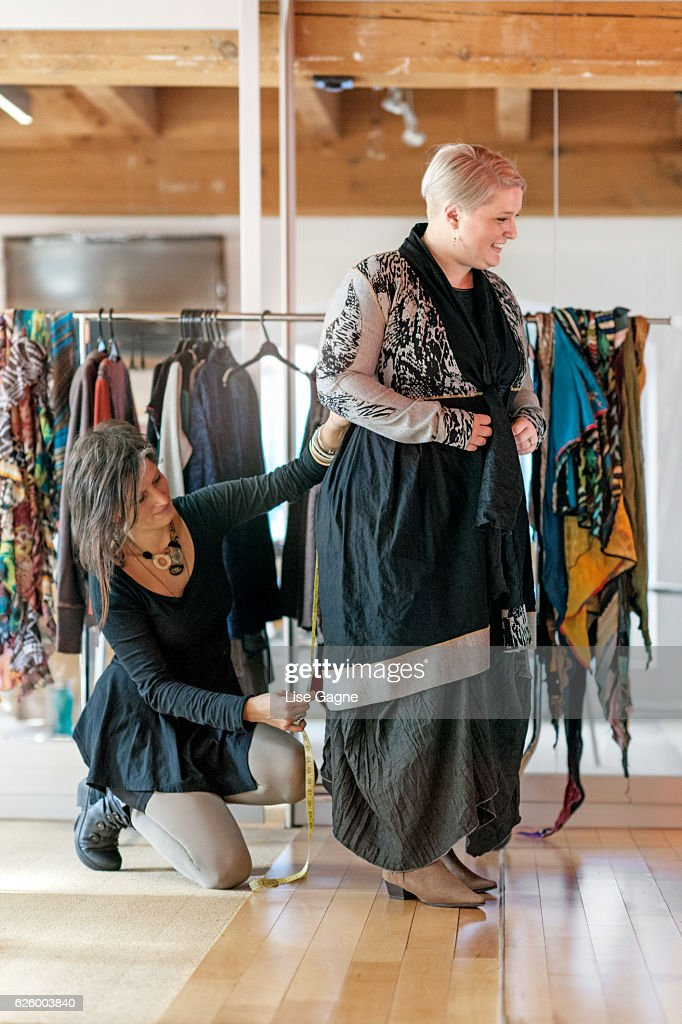 Fasion designer  taking customer measurement in clothing boutique : Foto de stock