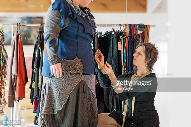 Fasion designer  taking customer measurement in clothing boutique