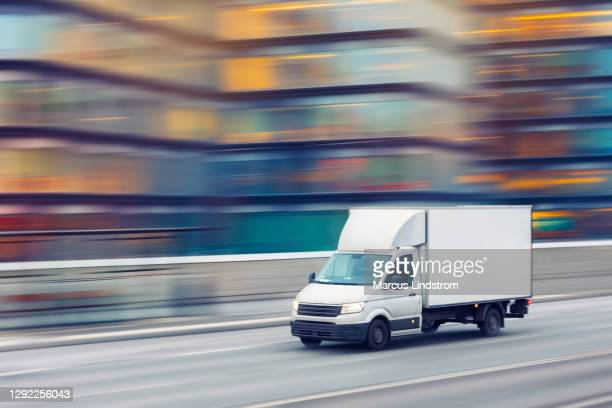 fast delivery truck travelling through the city streets - box container stock pictures, royalty-free photos & images