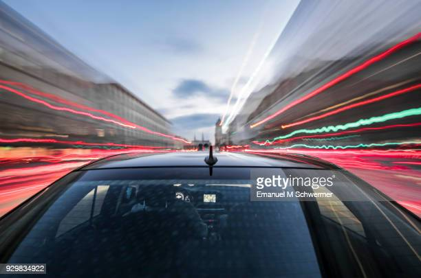 fast driving black German car with reflections and the rear window in foreground