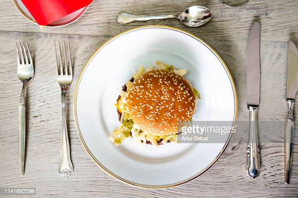 fast food deluxe with hamburger and french fries served with silver cutlery. - french fries stock pictures, royalty-free photos & images