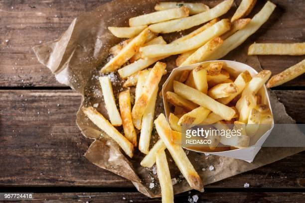 Fast food french fries potatoes with skin served with salt and herbs in lunch box on baking paper over old dark wooden background Top view space for...