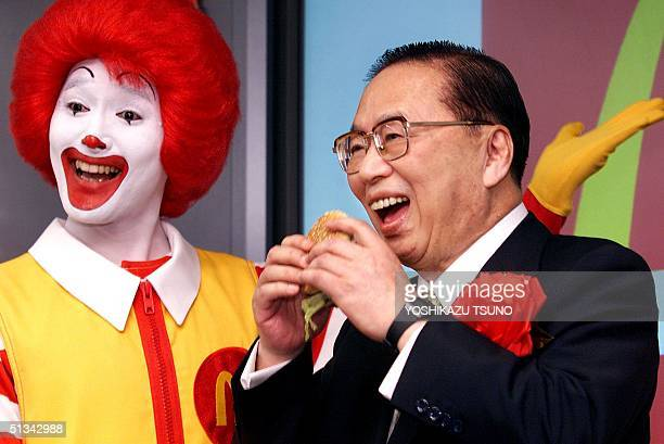 Fast food giant McDonald's president, Den Fujita bites into a BigMac as the company's stock is listed on the Jasdaq over-the-counter market in Tokyo,...