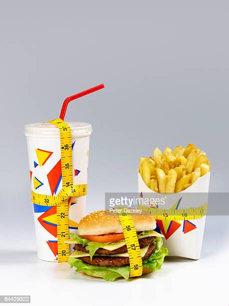 fast food meal with tape measure  - ready to eat stock pictures, royalty-free photos & images