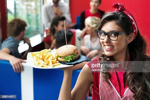 Camarera muestra de comida rápida con una hamburguesa. Amigos en el fondo