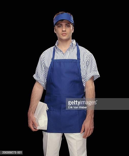Fast food worker holding paper bag, portrait, close-up