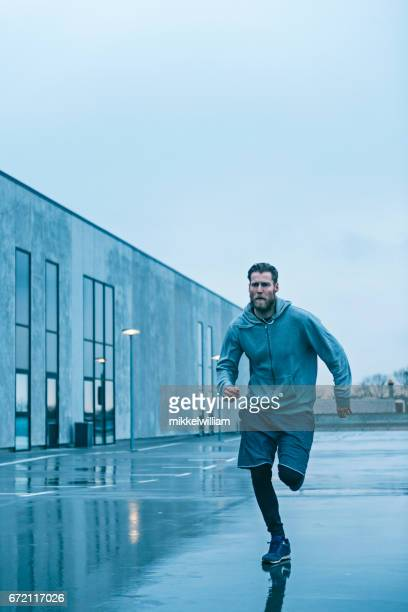Fast male runner sprints on wet streets after rain