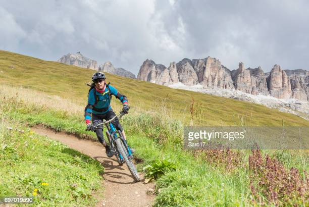 fast mountainbiking on narrow turn, dolomites, italy - cross country cycling stock photos and pictures